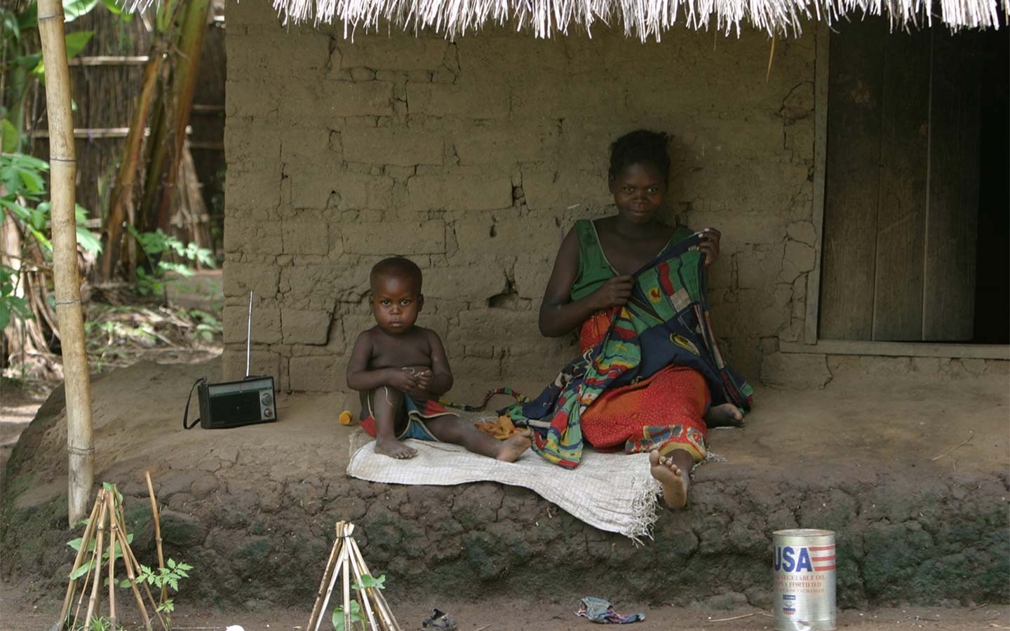 Mother and child listening to radio in front of simple home.