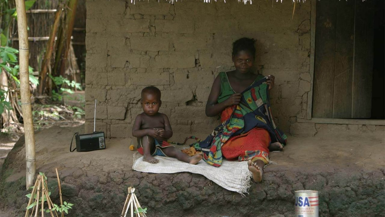 A mother and her child sit at their home next to a radio.