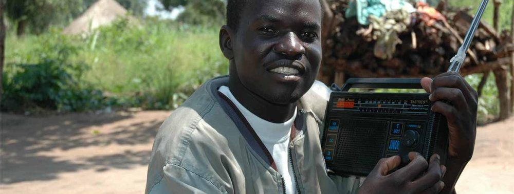 Smiling African man using a portable radio.