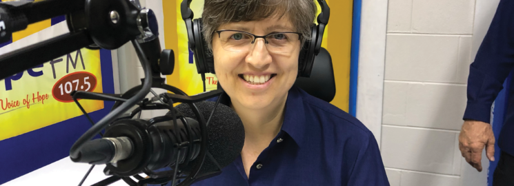 Lady sitting in a radio studio with earphones on